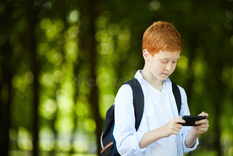 使用与电话的男小学生 图库摄影