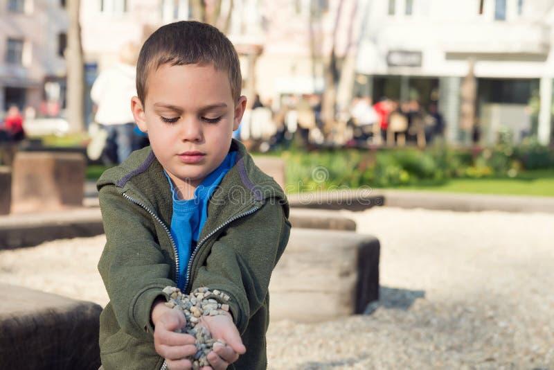 使用与石头的孩子在公园 库存照片