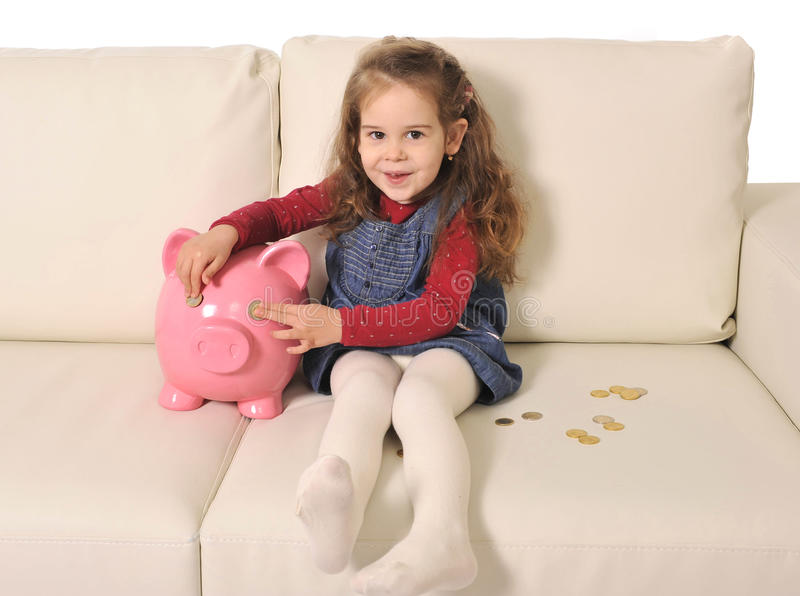 使用与硬币和巨大的存钱罐的逗人喜爱的小女孩沙发的 免版税库存图片
