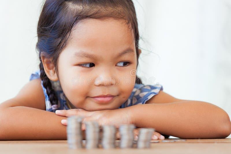 十四小女孩做爰相片_使用与硬币的逗人喜爱的亚裔小女孩做堆金钱. 浓度, 无罪.