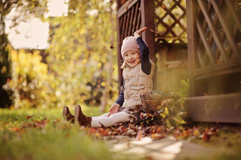 使用与秋叶和投掷他们的美丽的愉快的儿童女孩 免版税库存图片