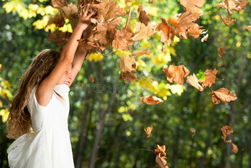 使用与秋叶的女孩户外。 免版税库存照片
