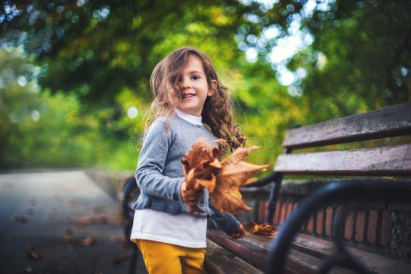 使用与秋天叶子的美丽的女孩在秋天公园 库存照片