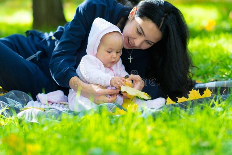 使用与秋天叶子的逗人喜爱的矮小的婴孩 库存照片