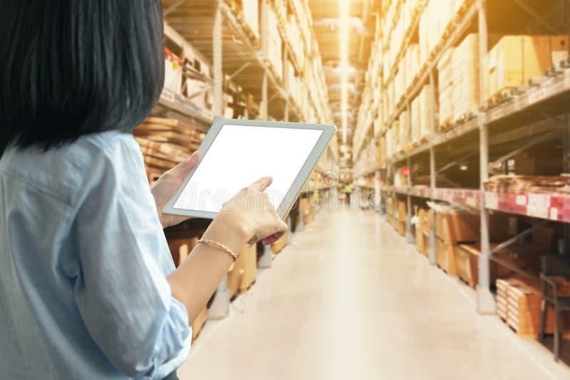 使用与空白白色桌面屏幕的妇女一平板电脑有在大仓库的 免版税图库摄影
