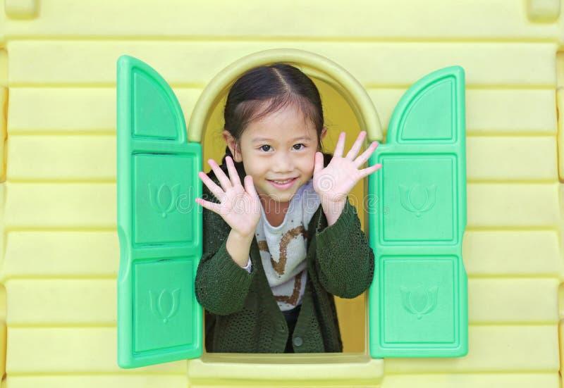 使用与窗口玩具剧场的可爱的矮小的亚裔儿童女孩在操场 库存图片