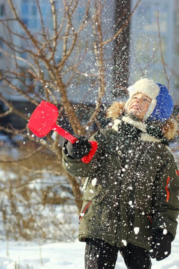 使用与第一冬天雪的七岁的白种人愉快的男孩画象  免版税库存图片
