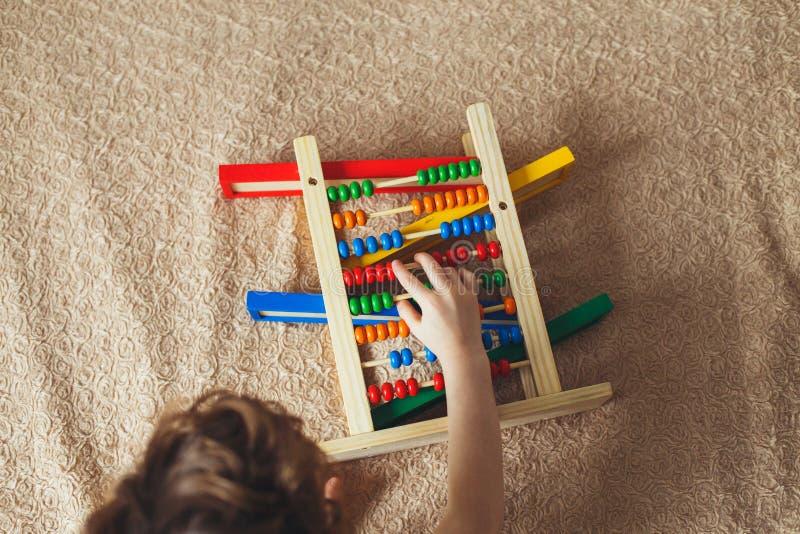 使用与算盘的小男孩的手 使用与木玩具的卷曲逗人喜爱的小孩的图片的Clouse 儿童教育 免版税库存图片