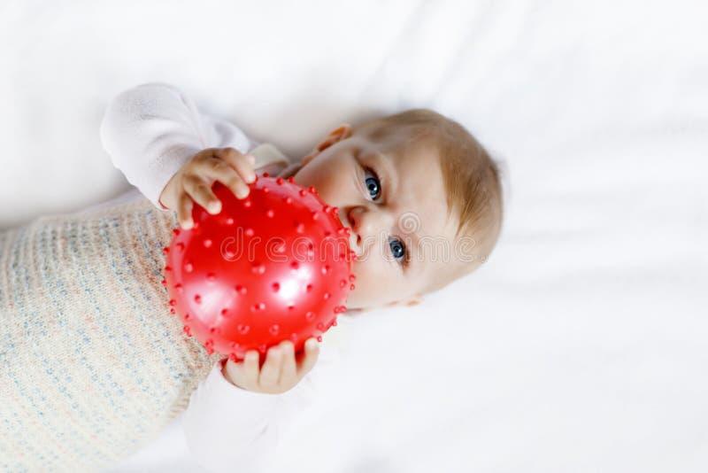 使用与红树胶球的逗人喜爱的婴孩 婴儿,获得的小女孩乐趣,劫掠和爬行 家庭,新的生活 免版税库存图片