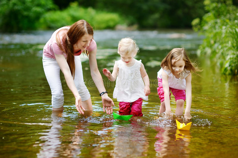 使用与纸小船的两个姐妹和他们的妈妈 免版税库存图片