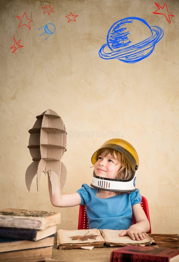 使用与纸板玩具火箭的孩子 免版税库存照片