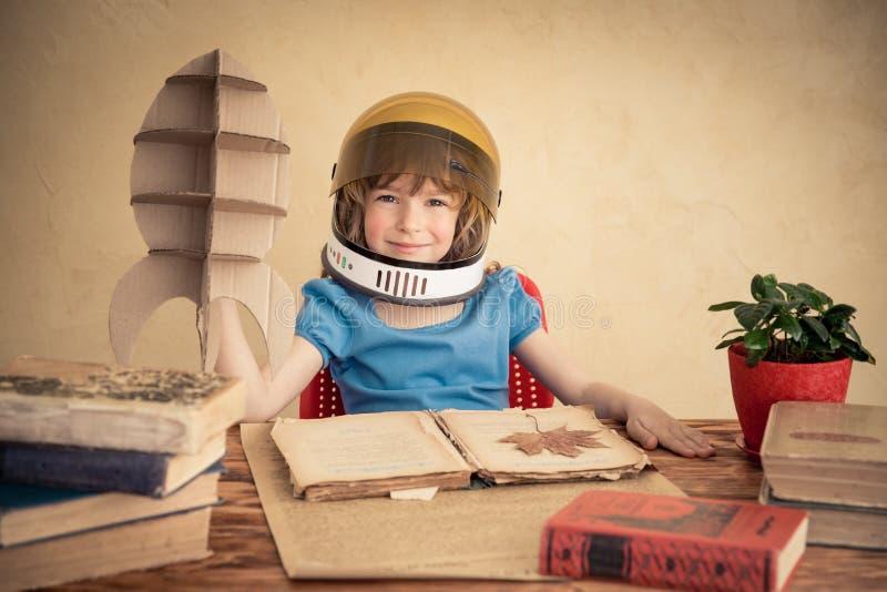 使用与纸板玩具火箭的孩子 免版税库存图片
