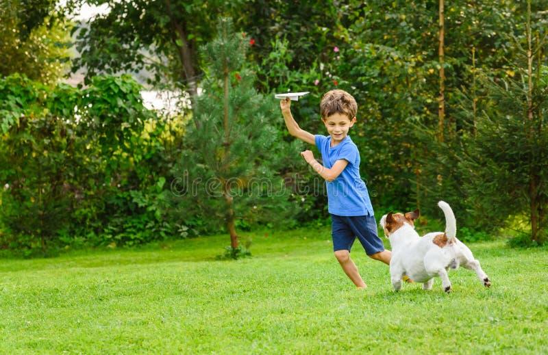 使用与纸飞机和狗户外的孩子在后院草坪 库存照片