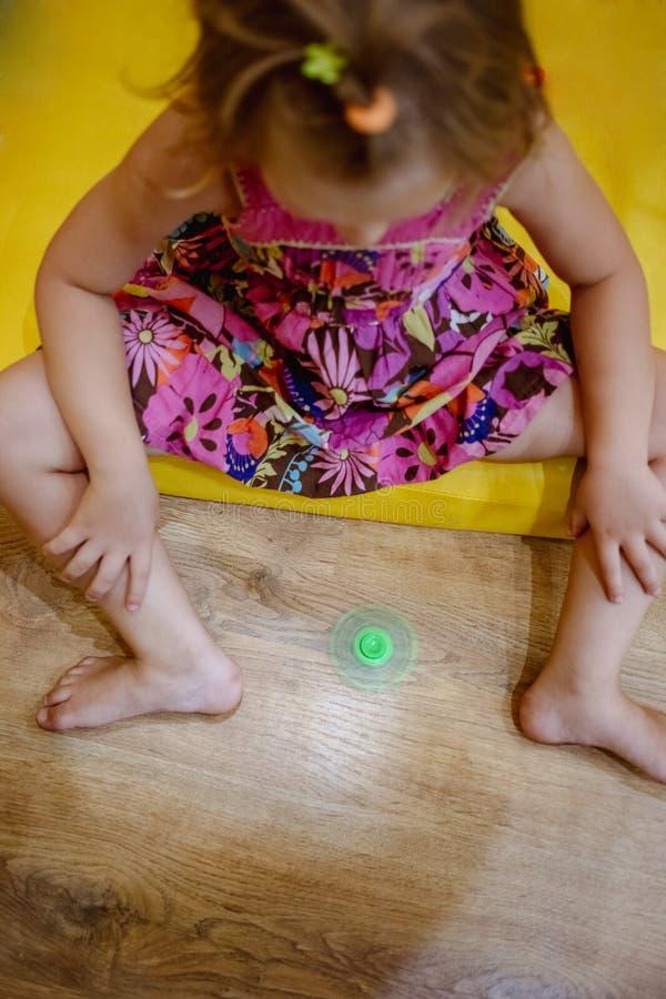 使用与绿色坐立不安锭床工人玩具的小女孩 免版税图库摄影