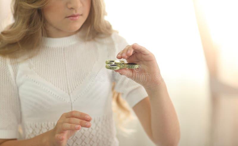 使用与绿色坐立不安锭床工人的逗人喜爱的年轻小女孩在明亮的屋子里 图库摄影