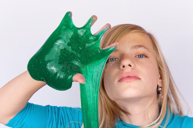 使用与绿色软泥看起来的滑稽的女孩在她的手上的泥状物质 库存图片