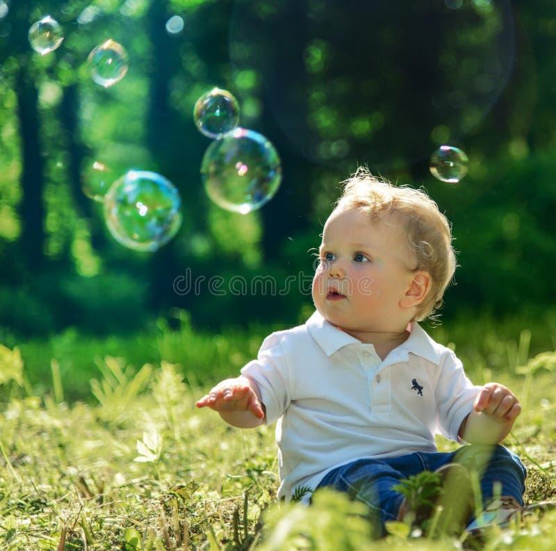 使用与肥皂泡的小男孩 免版税库存图片