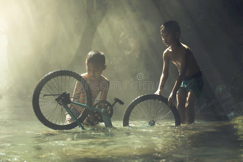 使用与自行车的孩子在The Creek 免版税库存照片