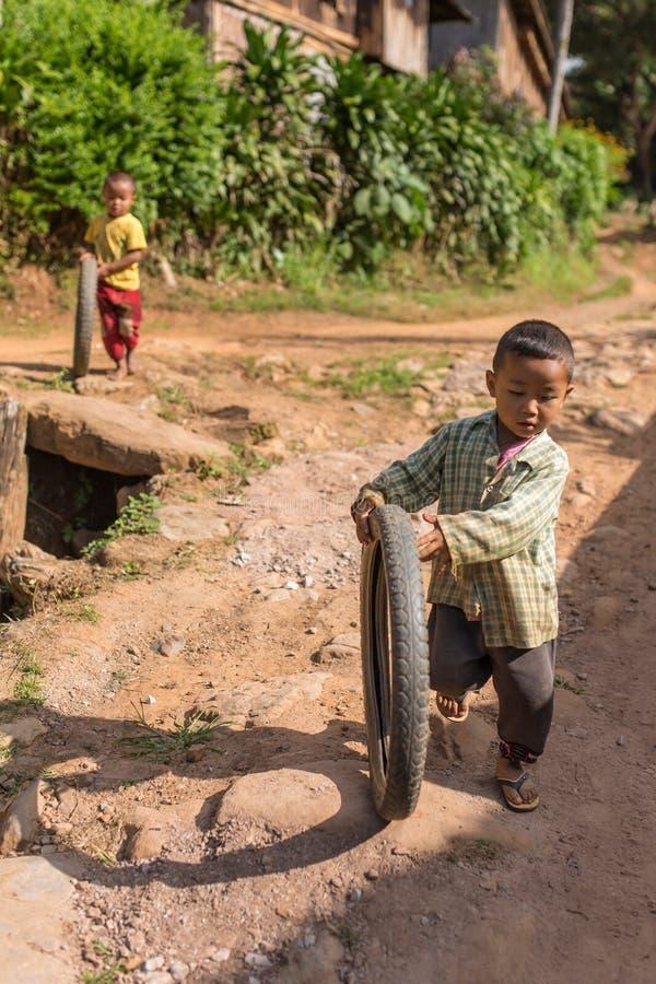 使用与自行车轮胎的小缅甸男孩在村庄在Hsipaw附近,缅甸 图库摄影