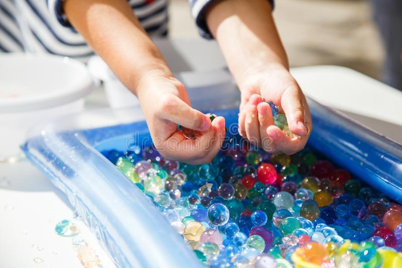 使用与色的玻璃球的孩子,打与色的球的比赛 免版税库存图片