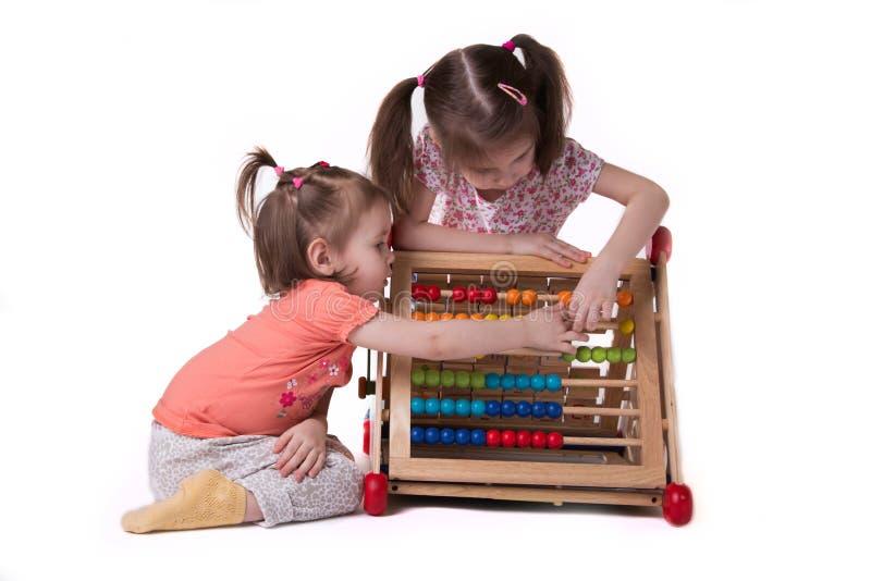 使用与色的票据坐的两个女孩 库存照片