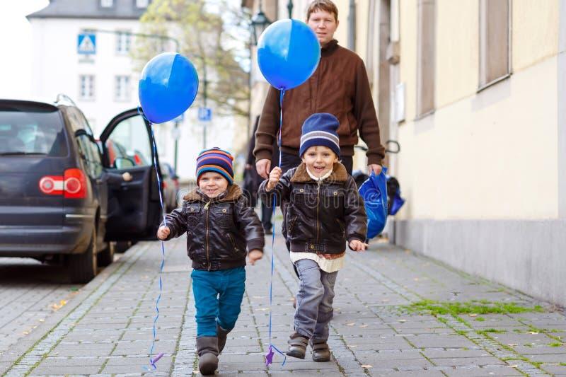 使用与蓝天气球的两个小孩男孩和爸爸户外 愉快的孪生和小孩兄弟和父亲,年轻 库存照片