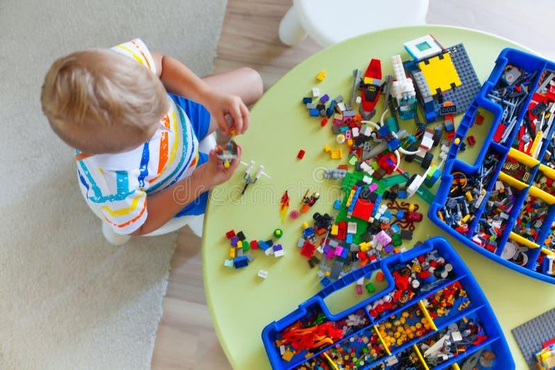 使用与许多的小白肤金发的孩子男孩五颜六色的塑料块 库存照片