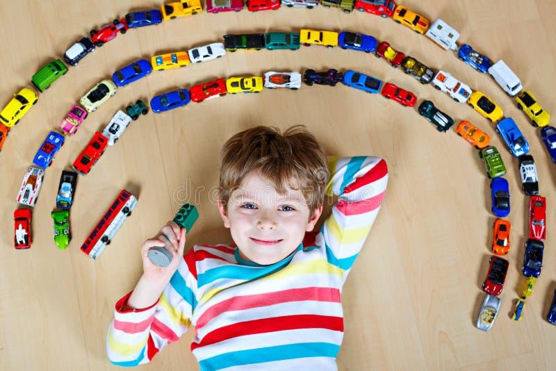 使用与许多的逗人喜爱的矮小的白肤金发的孩子男孩室内玩具汽车 穿五颜六色的衬衣的孩子 有愉快的学龄前儿童 库存图片