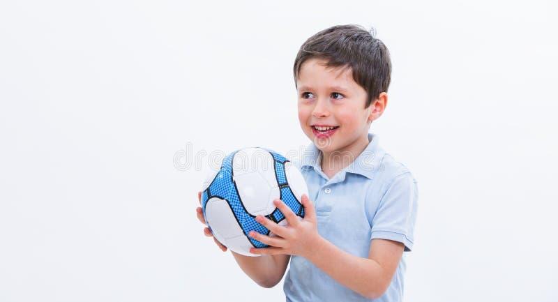 使用与足球的男孩,隔绝在白色演播室背景 孩子足球选手画象有球的在手中 年轻逗人喜爱 库存照片