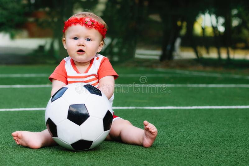 使用与足球的运动衫和红色发带的小小孩女孩在橄榄球场户外在夏日 免版税库存图片