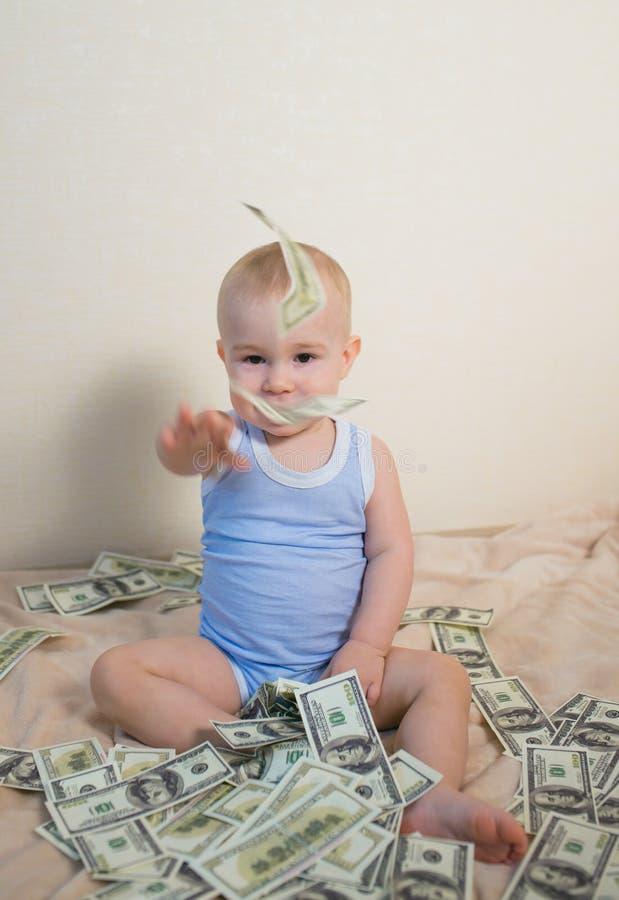 使用与金钱,美元投掷的hundreeds的逗人喜爱的男婴  库存照片