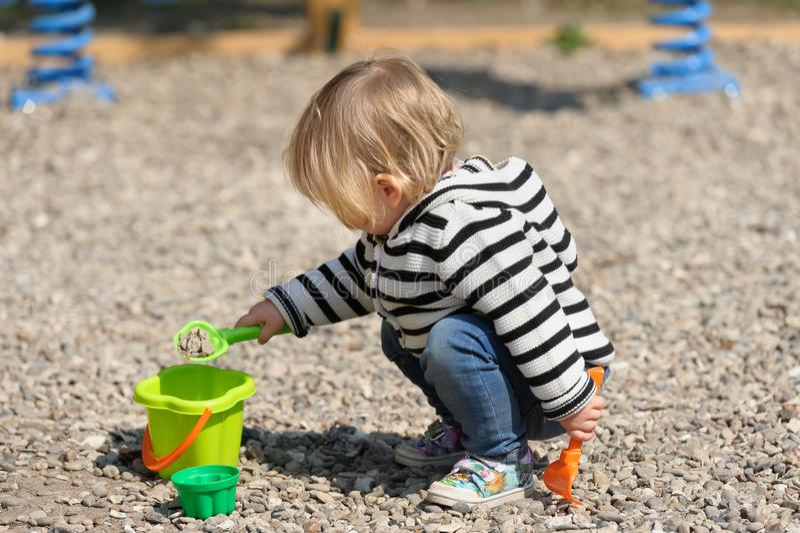 使用与铁锹的逗人喜爱的小孩女婴在操场 图库摄影