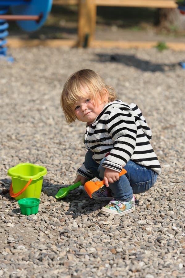 使用与铁锹的逗人喜爱的小孩女婴在操场 库存图片