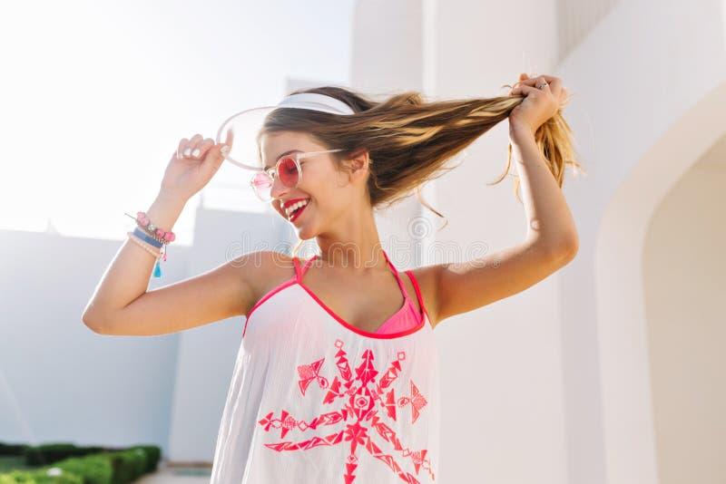 使用与长的浅褐色的头发的优美的激动的女孩看,站立在现代修造的背景 ?? 免版税库存照片