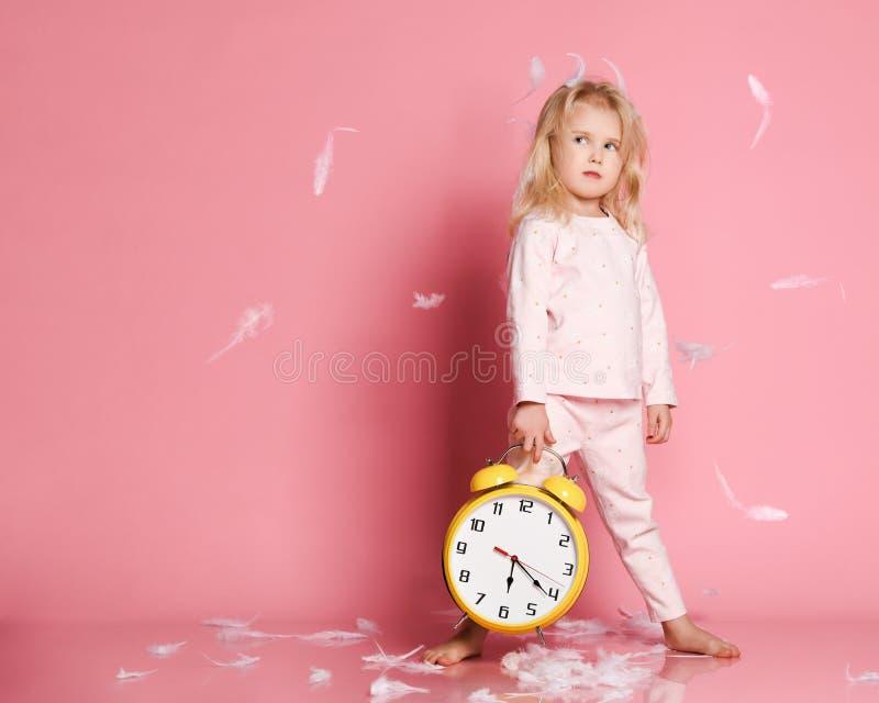 使用与闹钟的可爱的白肤金发的小孩 免版税库存照片