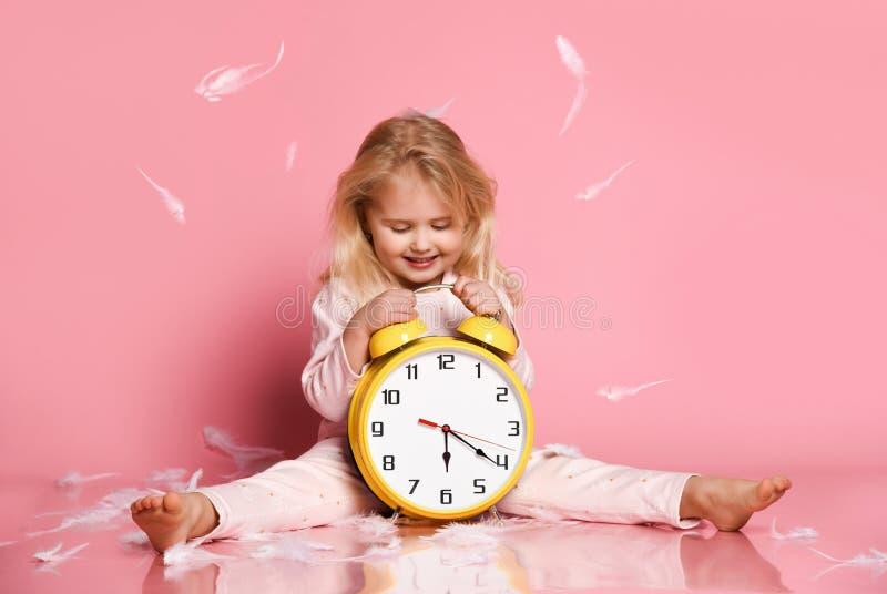 使用与闹钟的可爱的白肤金发的小孩 免版税图库摄影