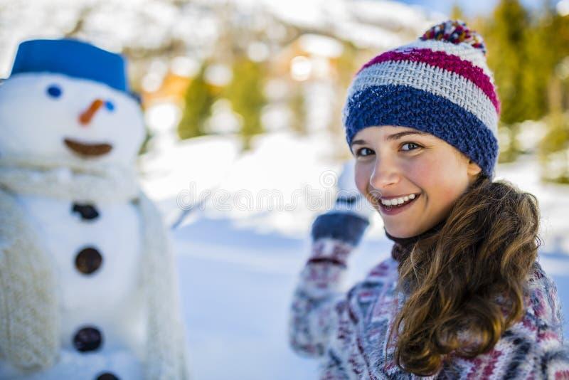 使用与雪人的愉快的微笑的十几岁的女孩 免版税库存照片