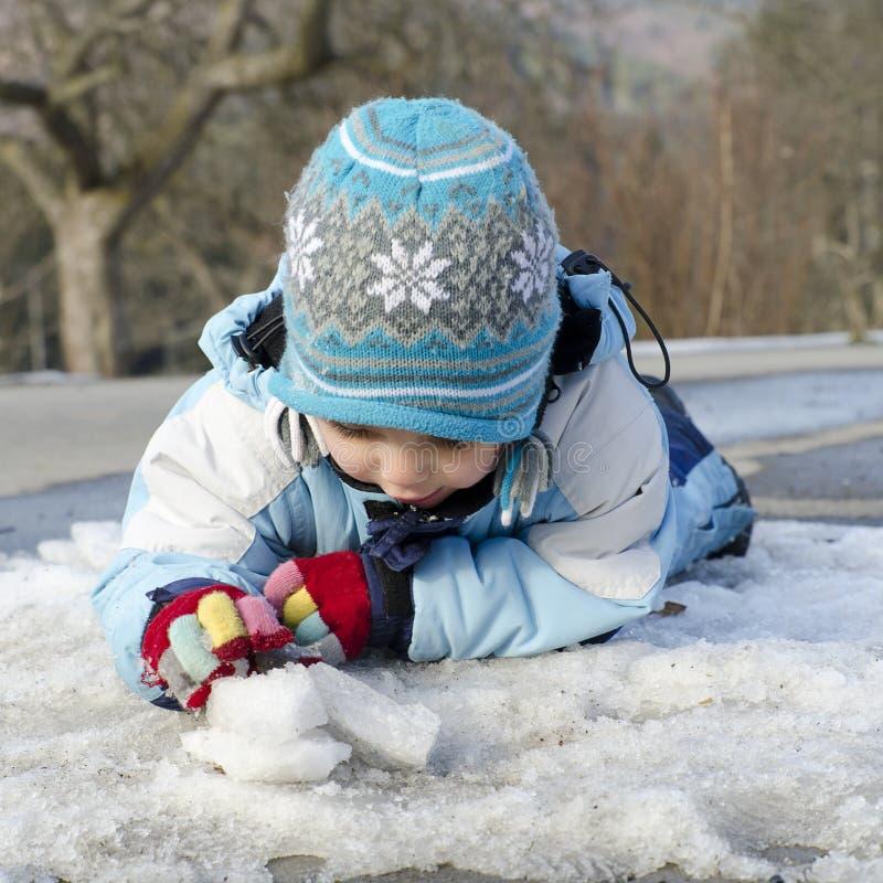 使用与雪和冰的孩子 免版税库存照片