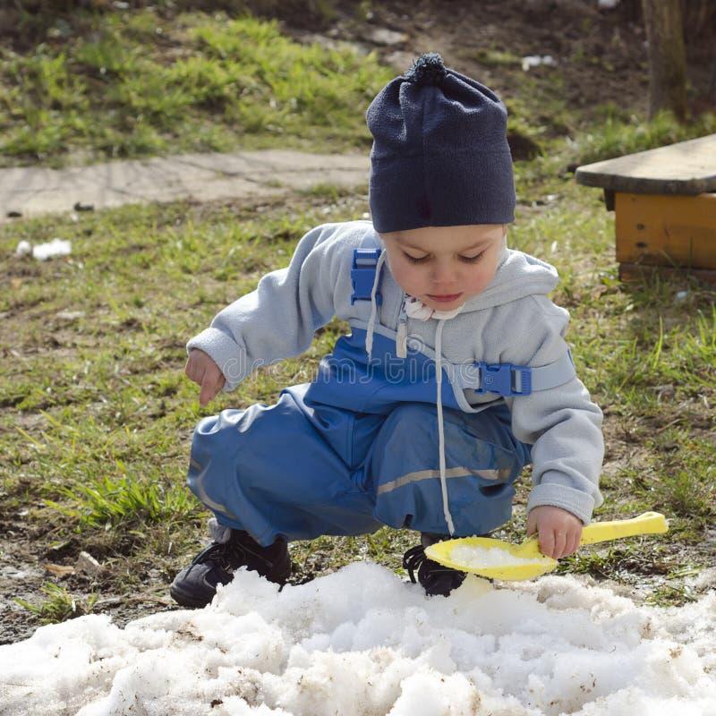 使用与雪的孩子在春天 库存图片