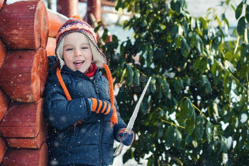 使用与雪的愉快的儿童男孩户外 在冬天步行的孩子佩带的衣服暖和 冬天多雪的天气 愉快的童年 冬天 免版税库存照片