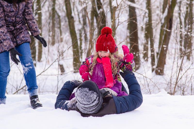 使用与雪的愉快的家庭在冬天森林里 免版税库存图片