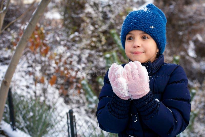 使用与雪的美丽的少女在公园 免版税库存照片