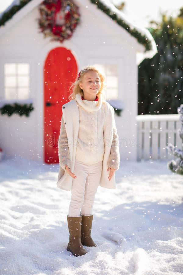 使用与雪的逗人喜爱的白肤金发的女孩在小屋和积雪的树附近 新年度和圣诞节时间 免版税库存照片