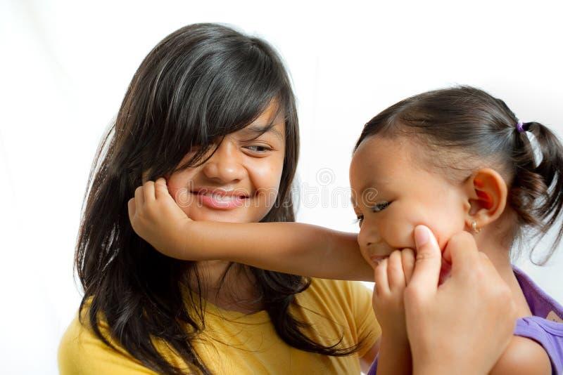 使用与青少年的姐妹一起的亚裔孩子 免版税库存照片