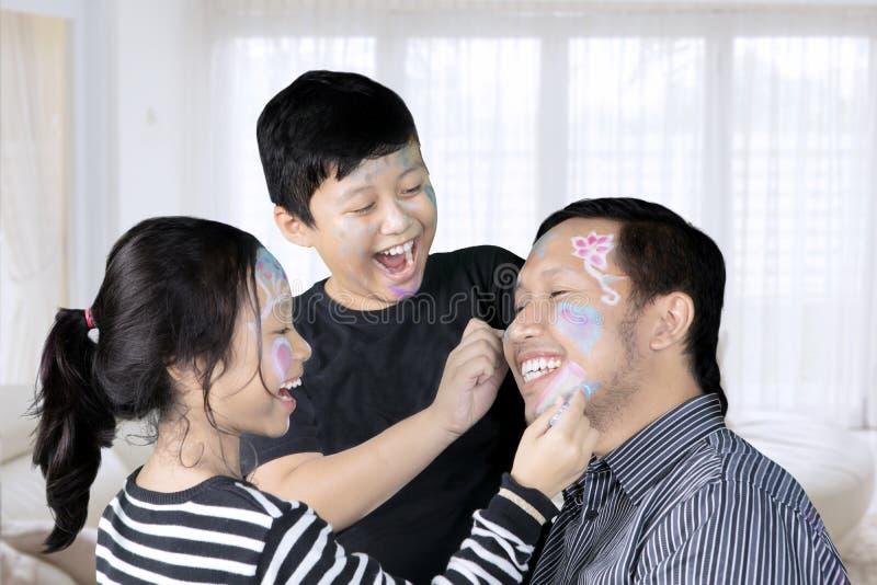 使用与面孔绘画的孩子和父亲 免版税库存照片