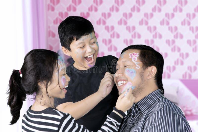使用与面孔绘画的父亲和孩子 免版税库存照片
