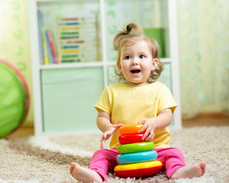 使用与颜色玩具的滑稽的孩子室内 图库摄影