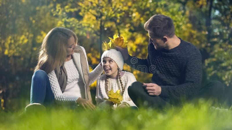使用与黄色叶子的幸福家庭在秋天公园,获得乐趣,父母身分 免版税库存照片