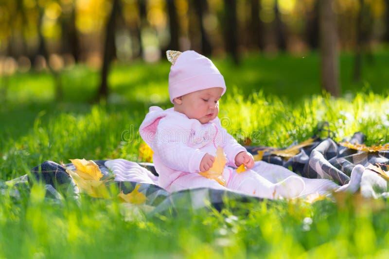 使用与黄色叶子的满足的女婴 库存图片