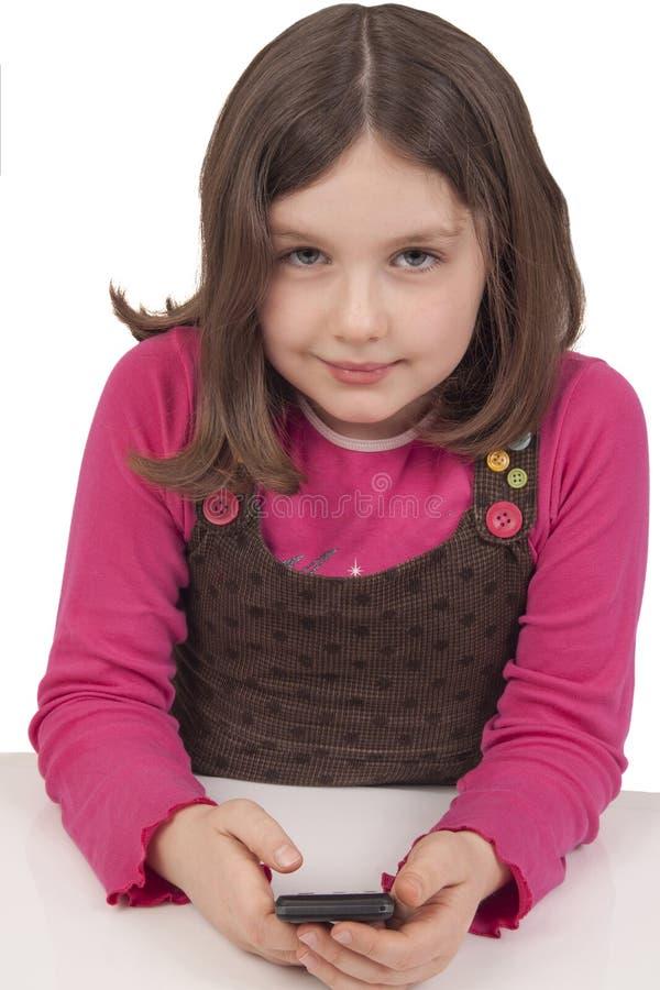 使用与移动电话的美丽的小女孩 免版税库存照片